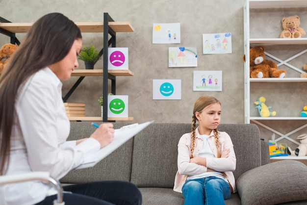 Depressed girl sitting on sofa with female psychologist writing note on clipboard Free Photo