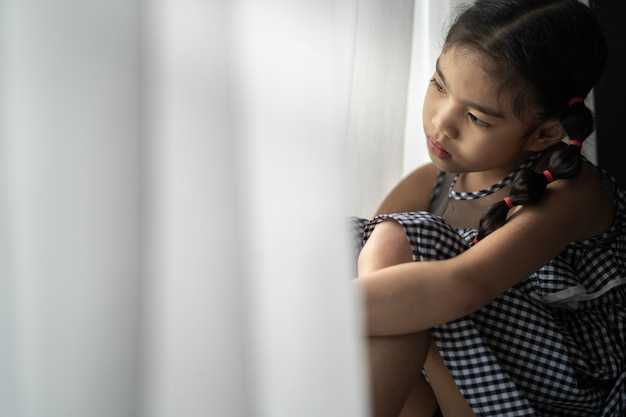 Depressed little girl near window at home, closeup Premium Photo