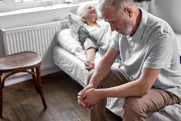 Подавленный мужчина сидит рядом со своей больной пожилой женой, лежащей на кровати, страдая от болезни. в больнице Premium Фотографии