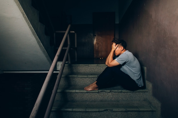 Depressed man sitting on the stairs in building and holding his forehead while having headache.depression concept Premium Photo