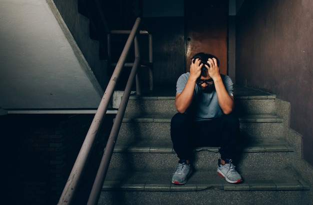 Depressed man sitting on the stairs in building and holding his forehead while having headache. Premium Photo