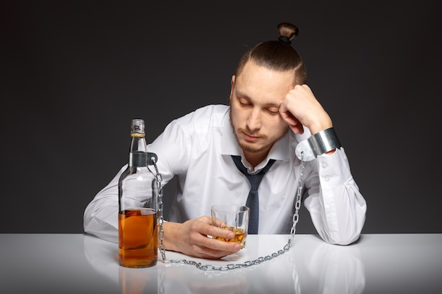 Depressed man spending time with a bottle of whiskey Free Photo