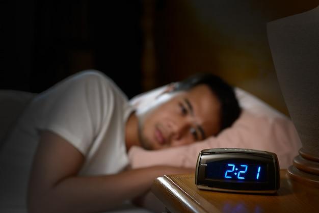 불면증으로 고통받는 우울한 남자가 침대에 누워 프리미엄 사진