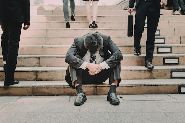 Depressed and tired businessman sitting at stair in city Premium Photo