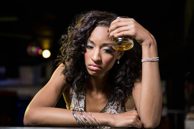 Depressed woman having whiskey drink at bar counter in bar Premium Photo