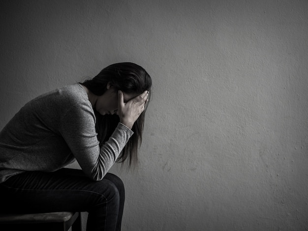 Depressed woman sitting on a chair in dark room at home. Premium Photo