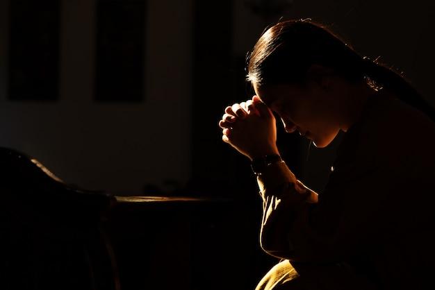 Подавленные женщины сидят в церкви при слабом освещении и молятся, концепция международного дня прав человека Premium Фотографии