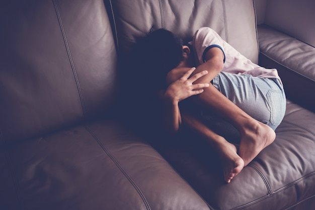 Depressed young boy sitting alone on sofa at home, children mental health Premium Photo