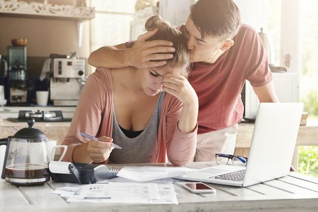 Подавленная молодая женщина, держащая ручку, расчет семейного бюджета Бесплатные Фотографии