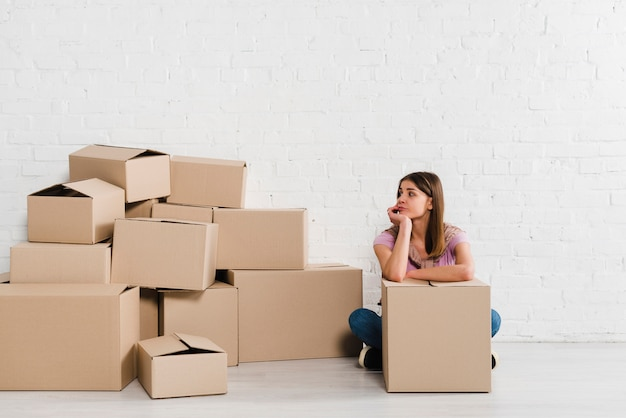 Depressed young woman looking at cardboard boxes Free Photo