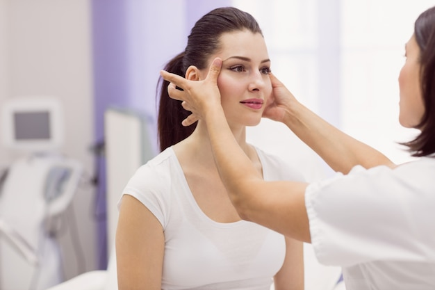 Dermatologist examining female patient skin Free Photo
