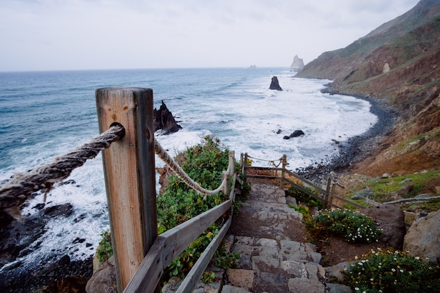 Descending rustic staircase leading to the a mountain shoreline Free Photo
