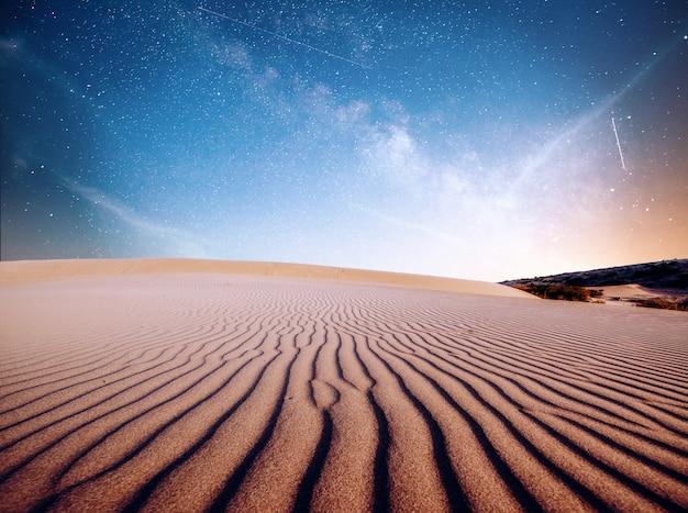 Пустынные песчаные дюны ночью, звезды и млечный путь, глубокое небо, астрофото Premium Фотографии