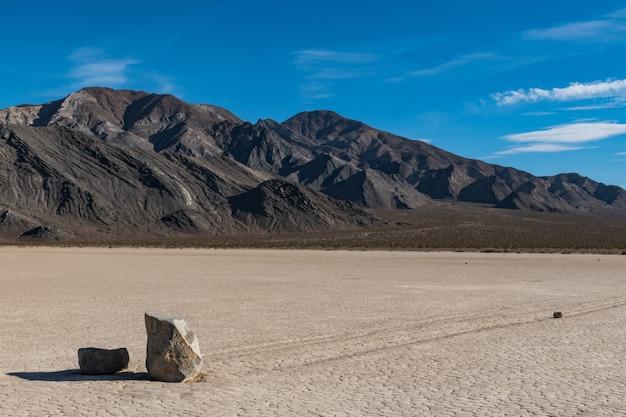 乾いた地面に2つの石と後ろの丘に長い痕跡が残る砂漠のシーン 無料写真