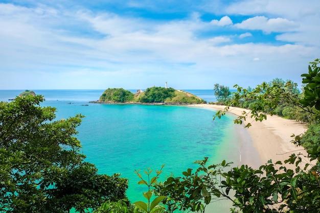 黄色いきれいな砂、ターコイズブルーの海、雲と青い空と人けのないビーチ Premium写真