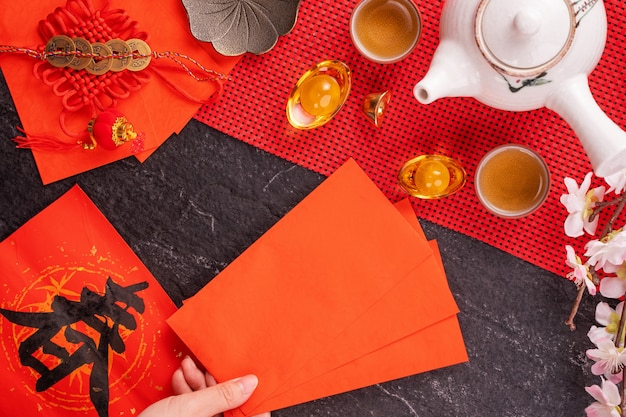 Design concept of chinese lunar january new year - woman holding, giving red envelopes (ang pow, hong bao) for lucky money, top view, flat lay, overhead above. the word 'chun' means coming spring. Premium Photo