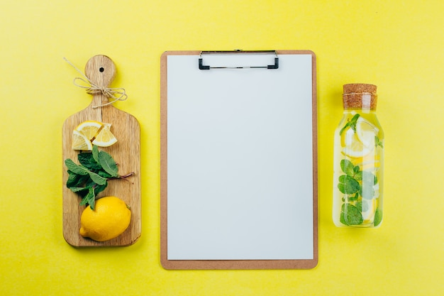 Design concept of mockup clip board and lemon mint water on yellow background. Premium Photo