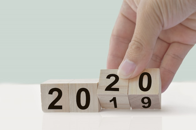 Design concept - new year 2019 change to 2020, hand change wooden cubes on white table. Premium Photo