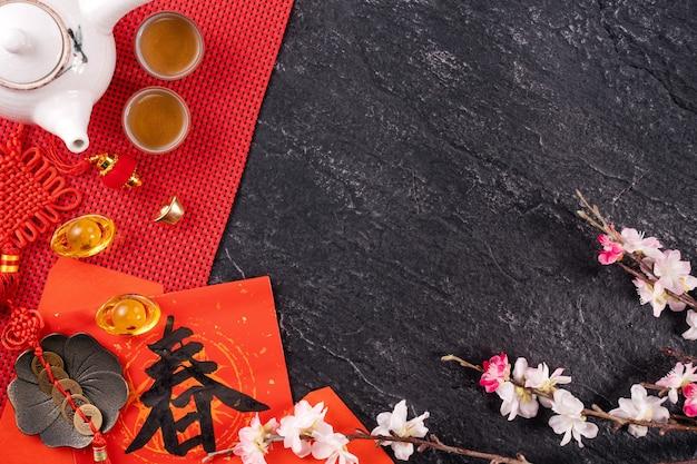 中国の太陰暦の1月の新年のデザインコンセプト-お祝いのアクセサリー、赤い封筒(ang pow、hong bao)、上面図、フラットレイ、頭上。 「チュン」という言葉は、春が来ることを意味します。 Premium写真