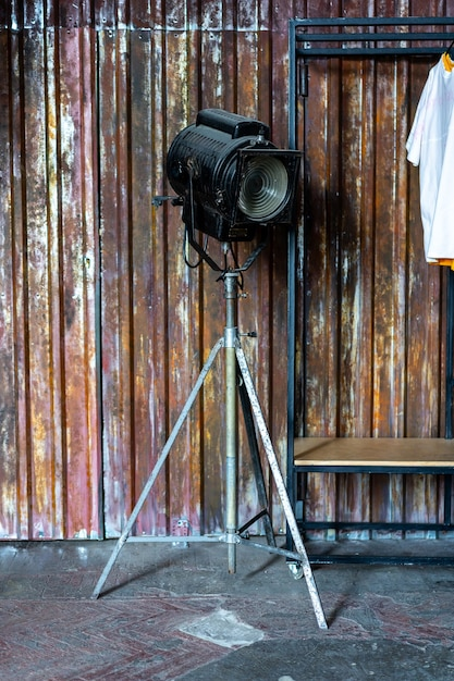 Design of loft interior of dressing room. metal wall and cinema lightning and white t-shirt on background. sunlight flare copyspace for text and design. Premium Photo