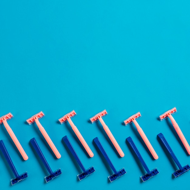 Design made with row of blue and pink razors on blue background Free Photo