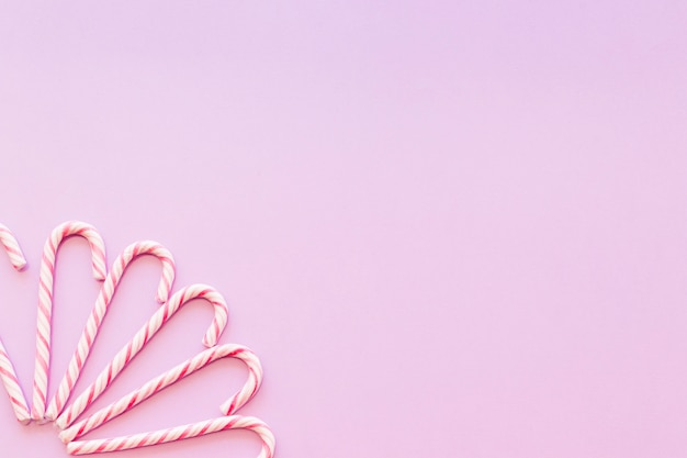 Design made with xmas candy cane on the pink background corner Free Photo