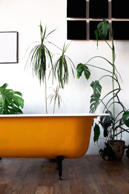 Дизайн лофта интерьер ванной комнаты или комнаты. белые стены со свободным пространством. тренд зеленый - пальмовые листья на фоне. желтая ванна современного дизайна. Premium Фотографии