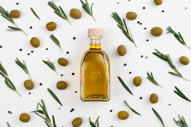 Design with leaves and olives arround oil bottle Free Photo