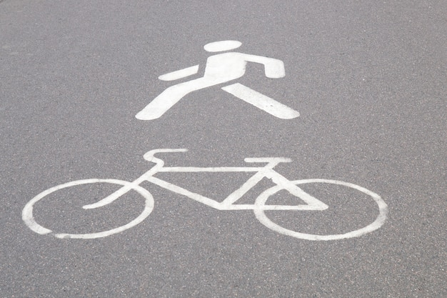 Designation of a bicycle path and pedestrian walkway painted in white paint on asphalt Premium Photo