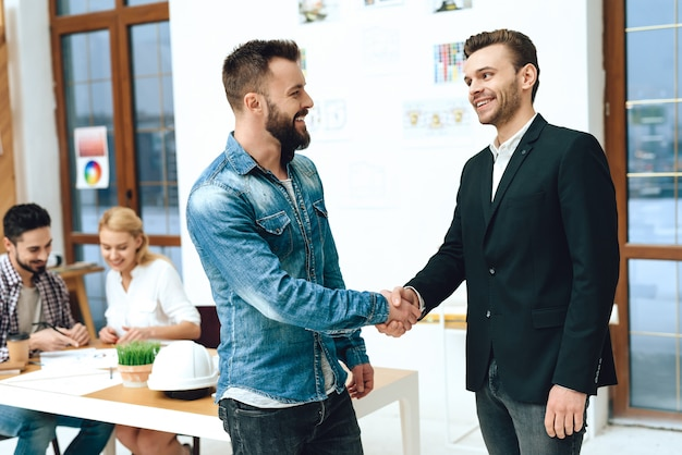 Designer and architect are shaking hands. Premium Photo
