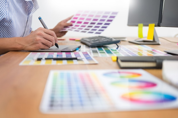 Designer editor at work drawing sketches a new project on graphic tablet and color palette Premium Photo