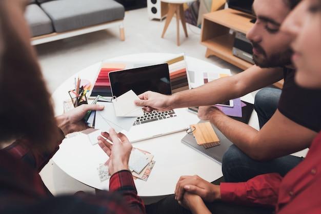 Designer and his clients are examining design patterns. Premium Photo