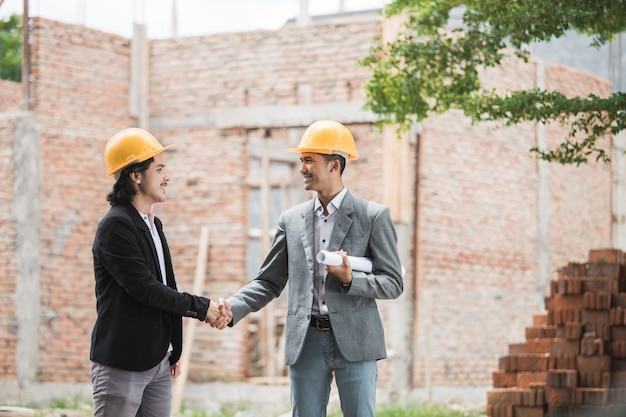 Designers discussing construction plan shaking hand Premium Photo