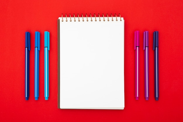 Desk arrangement with empty notepad on red background Free Photo