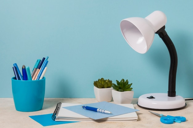 Desk arrangement with lamp and plants Free Photo
