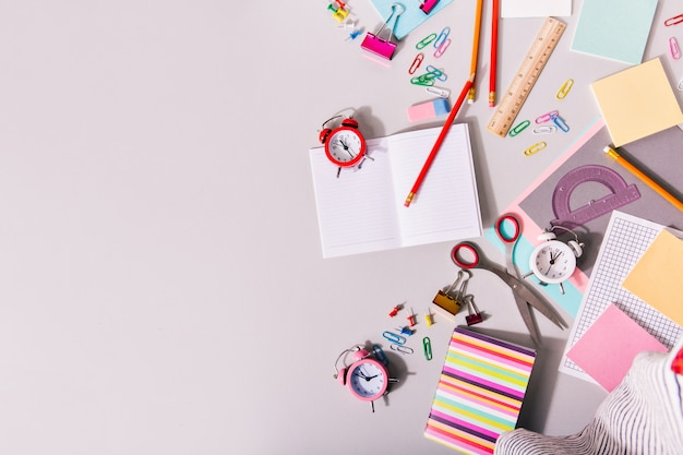 Desk covered with school supplies and colorful alarm clocks. Free Photo