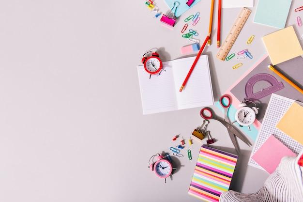 Scrivania ricoperta di materiale scolastico e sveglie colorate. Foto Gratuite