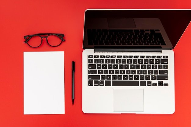 Desk elements with empty notebook on red background Free Photo
