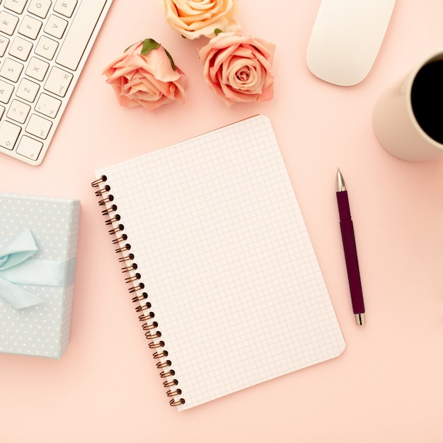 Desk table with pink roses, coffee cup,  blank spiral notebook, pen. top view, flat lay Free Photo