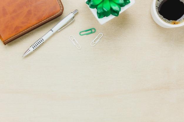 トップビュービジネスオフィスdesk.theノート、鉛筆、黒のコーヒー、木、木製のテーブルの背景にpaperclips。 無料写真