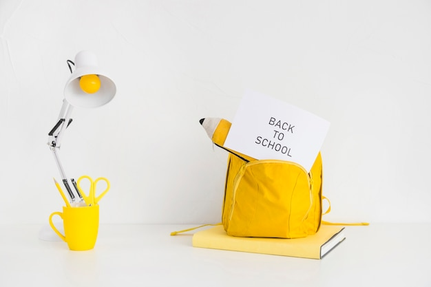 Desk with bright yellow backpack and pencil case Free Photo