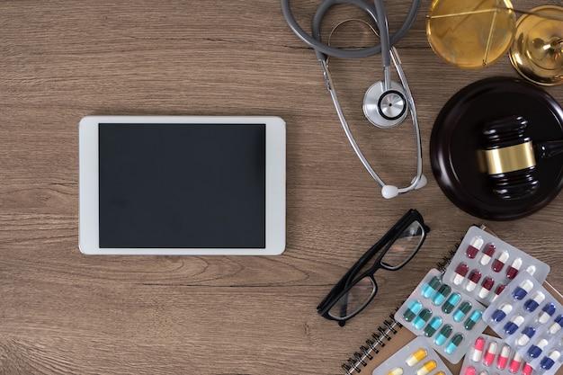 Стол с молотком, очки, планшет и лекарства Premium Фотографии