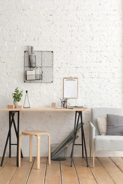 Desk with stationery in the white interior loft Premium Photo