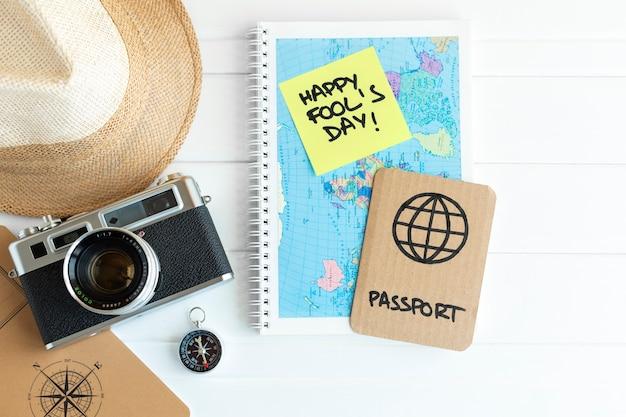 エイプリルフールのお祝いのジョークとして、段ボールのパスポートの横にカメラ、コンパス、帽子、地図などの旅行用品が置かれたデスク。テキスト用のスペース。 Premium写真