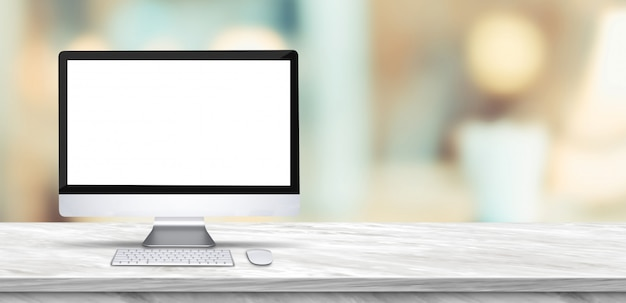 Desktop computer mock up on marble table and blurred soft light table in restaurant Premium Photo