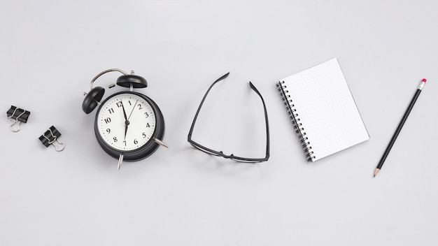 Desktop with a clock and office elements Free Photo