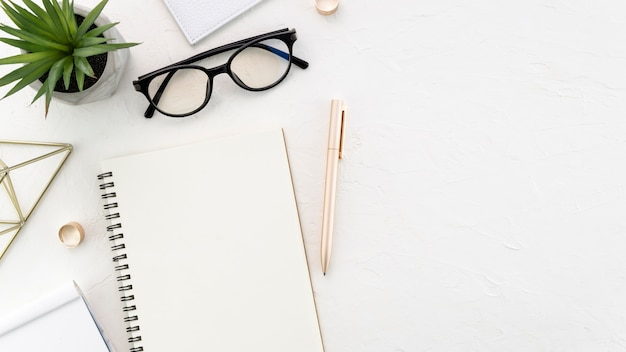 Desktop with glasses and notebook Free Photo