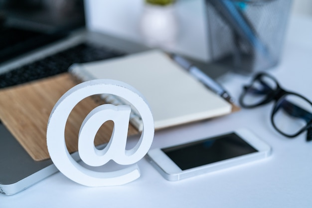 Desktop with notepad, smartphone, glasses and email symbol. Premium Photo