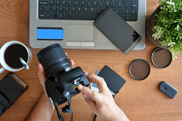 Desktop with photography equipment, camera, tripod,flash  and computer Premium Photo