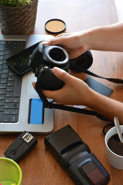 Desktop with photography equipment, camera, tripod,flash  and computer Premium Photo